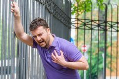 Man suffering from chest pain having heart attack or painful cramps royalty free stock photo