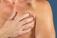 Man suffering from chest pain, having heart attack or painful cramps, pressing on chest with painful expression on blue. Severe heartache, man suffering from royalty free stock photography