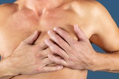 Man suffering from chest pain, having heart attack or painful cramps, pressing on chest with painful expression on blue stock photo
