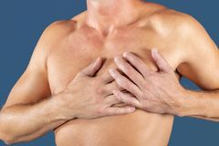 Man suffering from chest pain, having heart attack or painful cramps, pressing on chest with painful expression on blue backgound. stock images