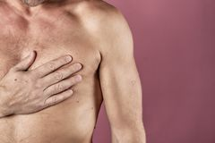 Man suffering from chest pain, having heart attack or painful cramps, pressing on chest with painful expression on pink backgound. stock images