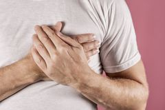 Man holding his chest with both hands, having heart attack or painful cramps, pressing on chest with painful expression on blue ba. Severe heartache, man stock photo