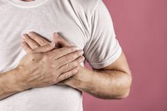 Man holding his chest with both hands, having heart attack or painful cramps, pressing on chest with painful expression on blue ba stock photography