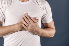 Man holding his chest with both hands, having heart attack or painful cramps, pressing on chest with painful expression on blue ba. Severe heartache, man stock photos