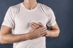 Man holding his chest with both hands, having heart attack or painful cramps, pressing on chest with painful expression on blue ba. Severe heartache, man royalty free stock photography