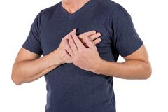 Man holding his chest with hands, having heart attack or painful cramps, pressing on chest with painful expression on white. Severe heartache, man suffering from royalty free stock photography