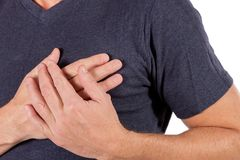 Man holding his chest with hands, having heart attack or painful cramps, pressing on chest with painful expression on white. Severe heartache, man suffering from stock photography