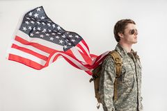 Earnest male soldier going to protect country. Severe military young man walking somewhere with serious look. He is having backpack on his shoulders and usa flag Stock Image