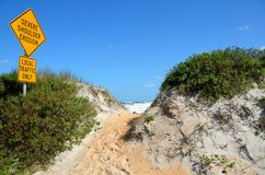 Severe shoulder beach erosion. Sign on beach with sea and blue sky background royalty free stock images