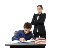 Severe teacher with arms folded standing behind the student's ba Royalty Free Stock Photography