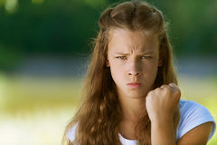 Severe teenage girl shakes her fist Stock Photography