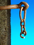 Severed Chain. A short length of rusty chain with the end link freshly sawed through and opened out so that the chain could be broken Royalty Free Stock Image