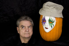 Severed Head with Pumpkin wearing a mask and a hat Stock Photo