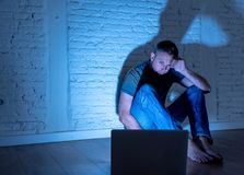 Men suffering Internet cyber bullying. Severely distraught young man with computer laptop suffering cyberbullying and harassment being online abused by stalker royalty free stock image