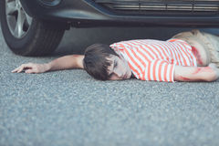 Severely injured boy laying down on street. Severely injured boy in striped shirt laying down on street with car stopped in front of him Stock Photos