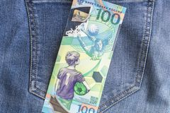 04.21.2019 Severodvinsk. Russia. Russian jubilee banknotes of FIFA 2018 soccer world cup 100 rubles on jeans background royalty free stock photo