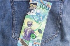 04 21 Severodvinsk 2019 Ryssland Ryska jubileumsedlar av den FIFA fotbollvärldscupen 2018 100 rubel på jeansbakgrund royaltyfri foto