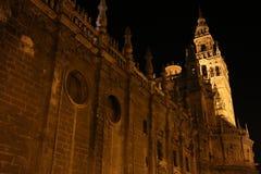 Sevilla Cathedral con la torre de Giralda en el fondo iluminado en la noche foto de archivo