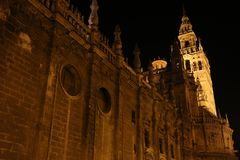 Sevilla Cathedral with the Giralda Tower in the background illuminated at night. The cathedral of Seville is the third largest in the world. The city of Stock Photo