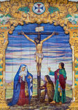 Sevilla - de ceramiektegel Kruisiging op de voorgevel van kerkbasiliek del Maria Auxiliadora Royalty-vrije Stock Foto