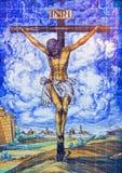 Sevilla - die keramische mit Ziegeln gedeckte Kreuzigung auf der Fassade der Kirche Iglesia de la Anunciacion an der Dämmerung Lizenzfreie Stockfotos
