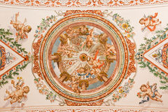 Sevilla - el fresco de ángeles con las insignias del papa en el techo en la iglesia Hospital de los Venerables Sacerdotes Fotos de archivo