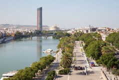 Sevilla - vooruitzichten van Torre del Oro om op de waterkant van de rivier van Guadalquivir te wandelen langs en moderne Torre C Stock Afbeelding