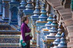 Seville Andalusia, Spanien - mars 25, 2008: unknowkvinna och detalj av majolicaen i plazaen av Spanien i Seville Royaltyfria Bilder