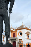 Seville Bullfight Arena. Fragment of matador statue against famous Seville bullfight arena, Spain Stock Image