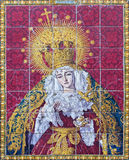 Seville - The ceramic tiled cried Madonna (Lady of Sorrow) on the facade of church Iglesia los Terceros. SEVILLE, SPAIN - OCTOBER 29, 2014: The ceramic tiled Stock Image