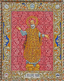 Seville - ceramic tiled Saint Philip Neri from 20. cent. by artist P. Navia on the facade of church Capilla de la Estrella. Royalty Free Stock Image