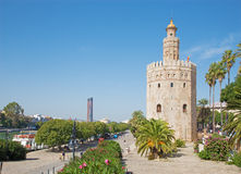 Seville - The medieval tower Torre del Oro, promenade and modern Torre Cajasol in background. Royalty Free Stock Photography