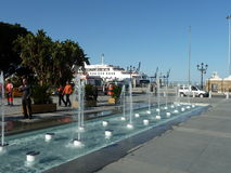 Seville Port, Spain. A view of Seville Port, Spain, with fountain, ship, ambulance and pedestrians Royalty Free Stock Photography