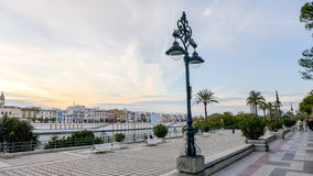 Seville - promenade. Seville, Spain - January 17, 2015: Promenade along the Guadalquivir river and modern Torre Cajasol in the background. Locals and tourists on Stock Photography