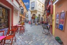 Seville - små gator med shoppar och restauranger i det Santa Cruz området Arkivfoton