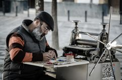 SEVILLE SPAIN. DECEMBER 2015. Street artist painting on a canvas. Full of color. Man unshaven with long beard and an old machine stock photo