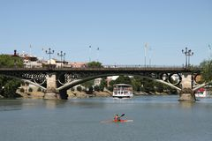 View of the Guadalquivir River and the Isabella II Bridge in Seville. SEVILLE, SPAIN - JULY 17, 2011: View of the Guadalquivir River and the Isabella II Bridge royalty free stock images