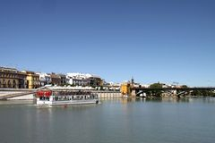 View of the Guadalquivir River and the Isabella II Bridge in Seville. SEVILLE, SPAIN - JULY 17, 2011: View of the Guadalquivir River and the Isabella II Bridge stock images