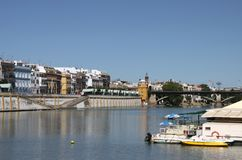 View of the Guadalquivir River and the Isabella II Bridge in Seville. SEVILLE, SPAIN - JULY 17, 2011: View of the Guadalquivir River and the Isabella II Bridge royalty free stock photos