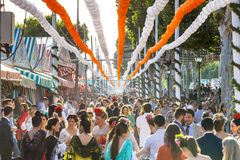 Crowd of people of all ages having fun and taking a walk at the Seville`s April Fair. Seville, Spain - May 03, 2017: Crowd of people of all ages having fun and stock image