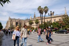 Tourists walking along the street near Seville Cathedral. royalty free stock images