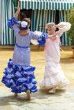 Women dressed in colourful flamenco dresses and dancing at the Seville April Fair. stock image