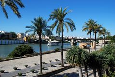 Triana bridge across the river, Seville, Spain. Pleasure boat on the Guadalquivir river with the Triana bridge to the rear, also known as the Isabel II bridge stock image