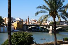 Triana bridge across the river, Seville, Spain. Rowers on the Guadalquivir river with the Triana bridge to the rear, also known as the Isabel II bridge, Seville royalty free stock image