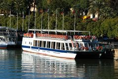 Tour boats moored along the river, Seville, Spain. Tour boats moored along the Guadalquivir river, Seville, Seville Province, Andalusia, Spain, Europe stock images