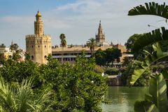 Seville, Spain - Sept. 23, 2013: Torre del Oro with the La Giralda in the distance and the river in the foreground royalty free stock image