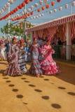 Kvinnor i flamenco utformar klänningen på Seville'sens den April mässan Arkivbild