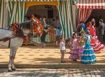 Ung flicka i flamenco utformar klänningen på Seville'sens den April mässan Arkivbild