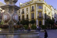 Seville Spanien, Januari 11, 2019: Closeup av springbrunnen på Virgenen de Los Reyes Plaza och ärkebiskopen Palace med turister arkivfoto
