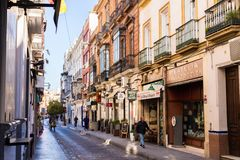 Seville, Spanien, Januari 11, 2019 - en gata med traditionella fasader av hus med vridna smidesjärnbalkonger och en gränd av royaltyfria foton